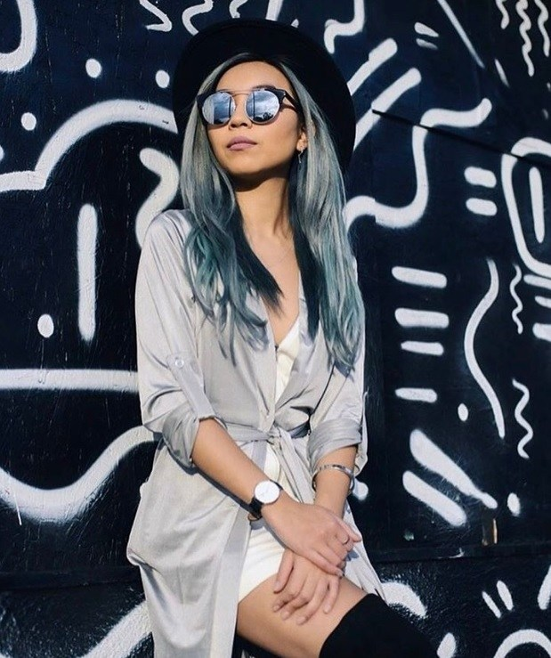 woman with long wavy ice blue metallic denim hair colour leaning against a black and white art wall with black hat and tinted sunglasses