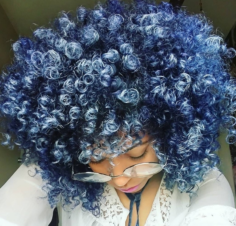 woman with curly afro ombre blue denim hair colour looking down wearing glasses