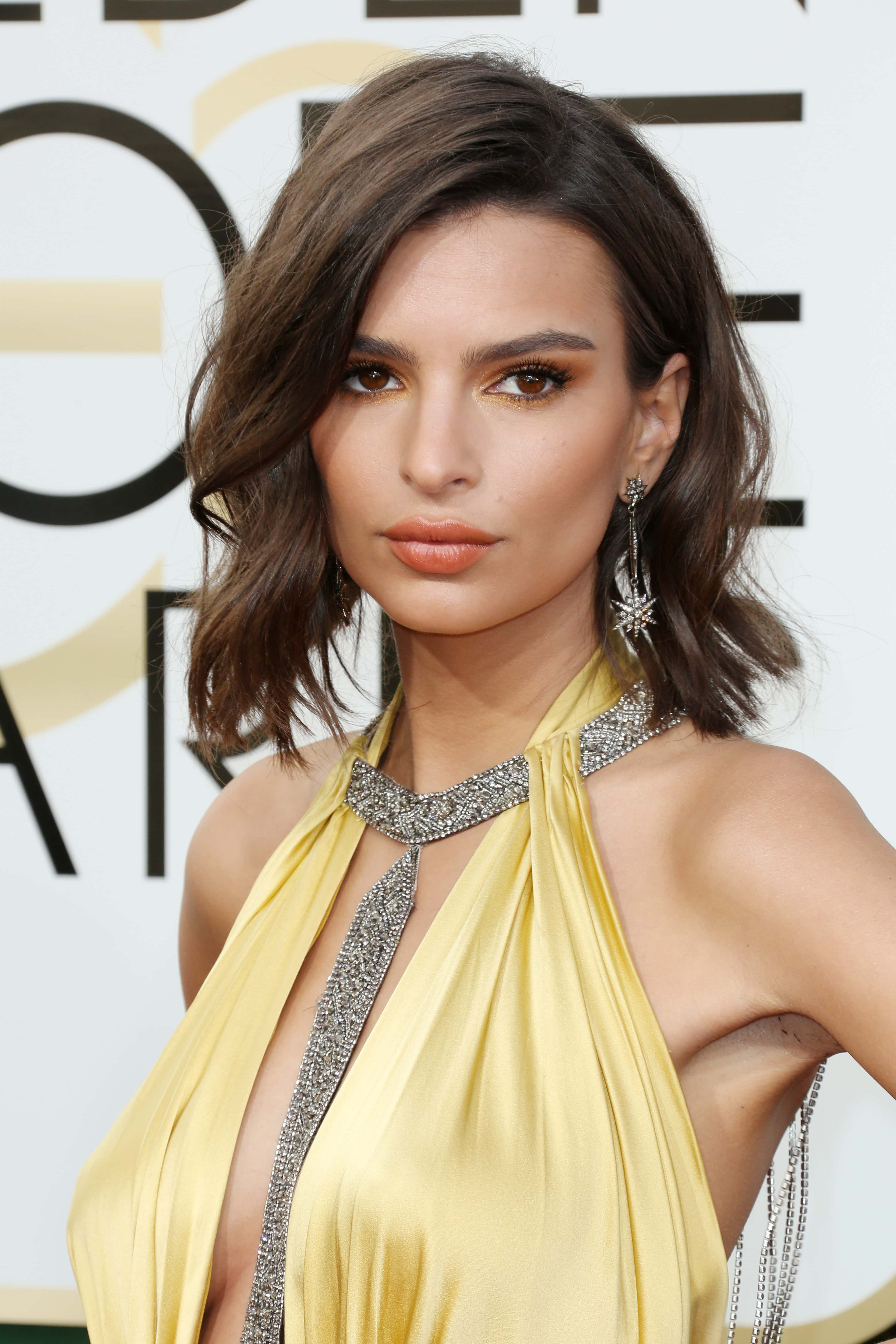close up shot of Emily Ratajkowski with wavy brown bob hairstyle, wearing yellow dress on the golden globes awards red carpet