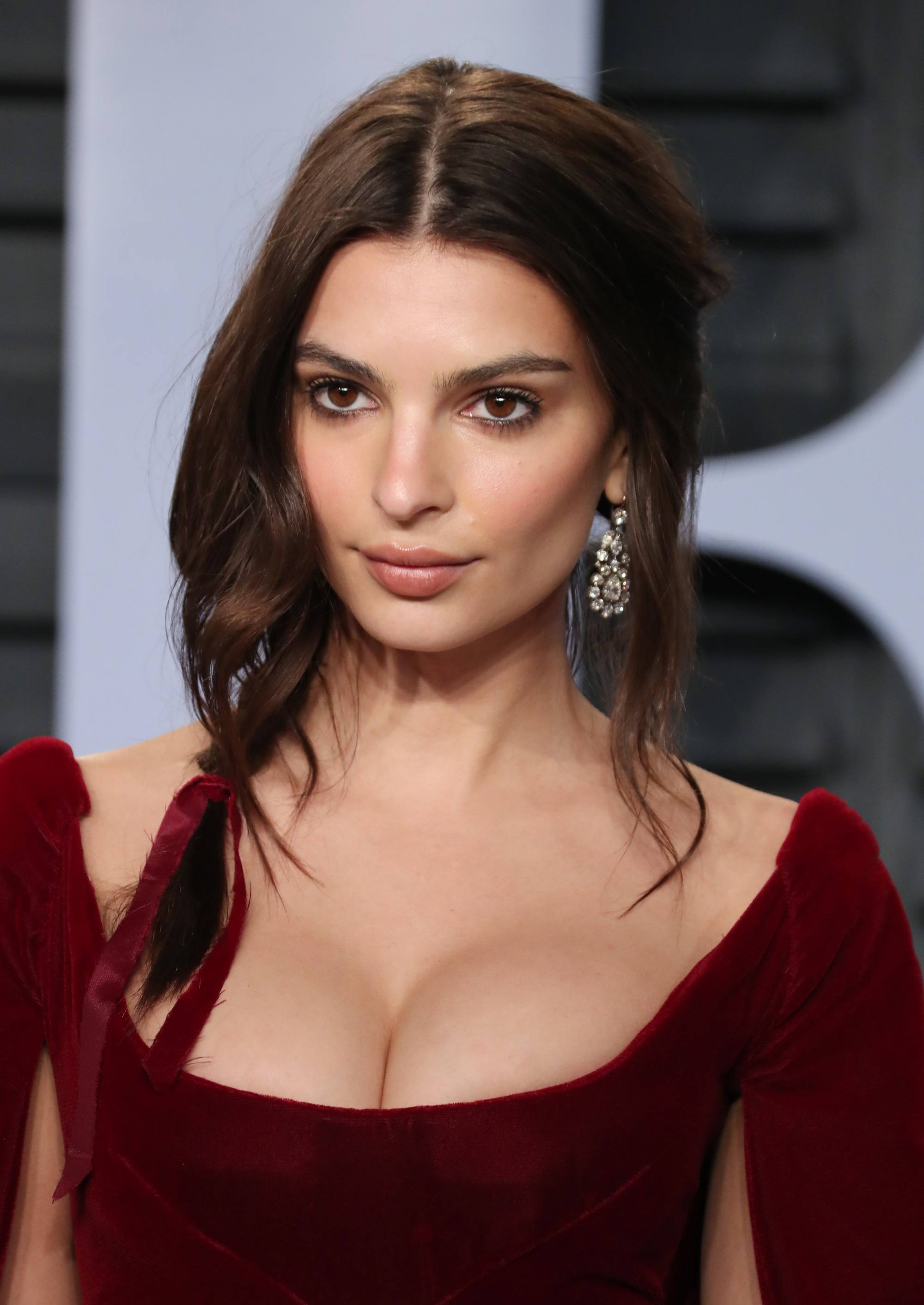 Side hairstyles: Emily Ratajkowski with her dark hair in a side braid with a red velvet ribbon, wearing a matching red velvet dress