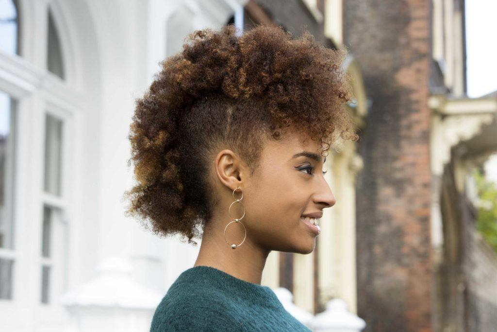 natural hairstyles: close up shot of a woman with caramel brown natural hair styled into a 'frohawk, wearing a green jumper and posing in the street