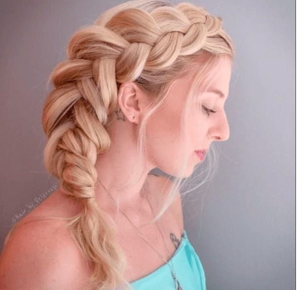 side view image of a woman with blonde hair in bouffant braids