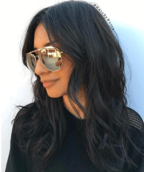 side view of a woman with black hair, sunglass and curled hair