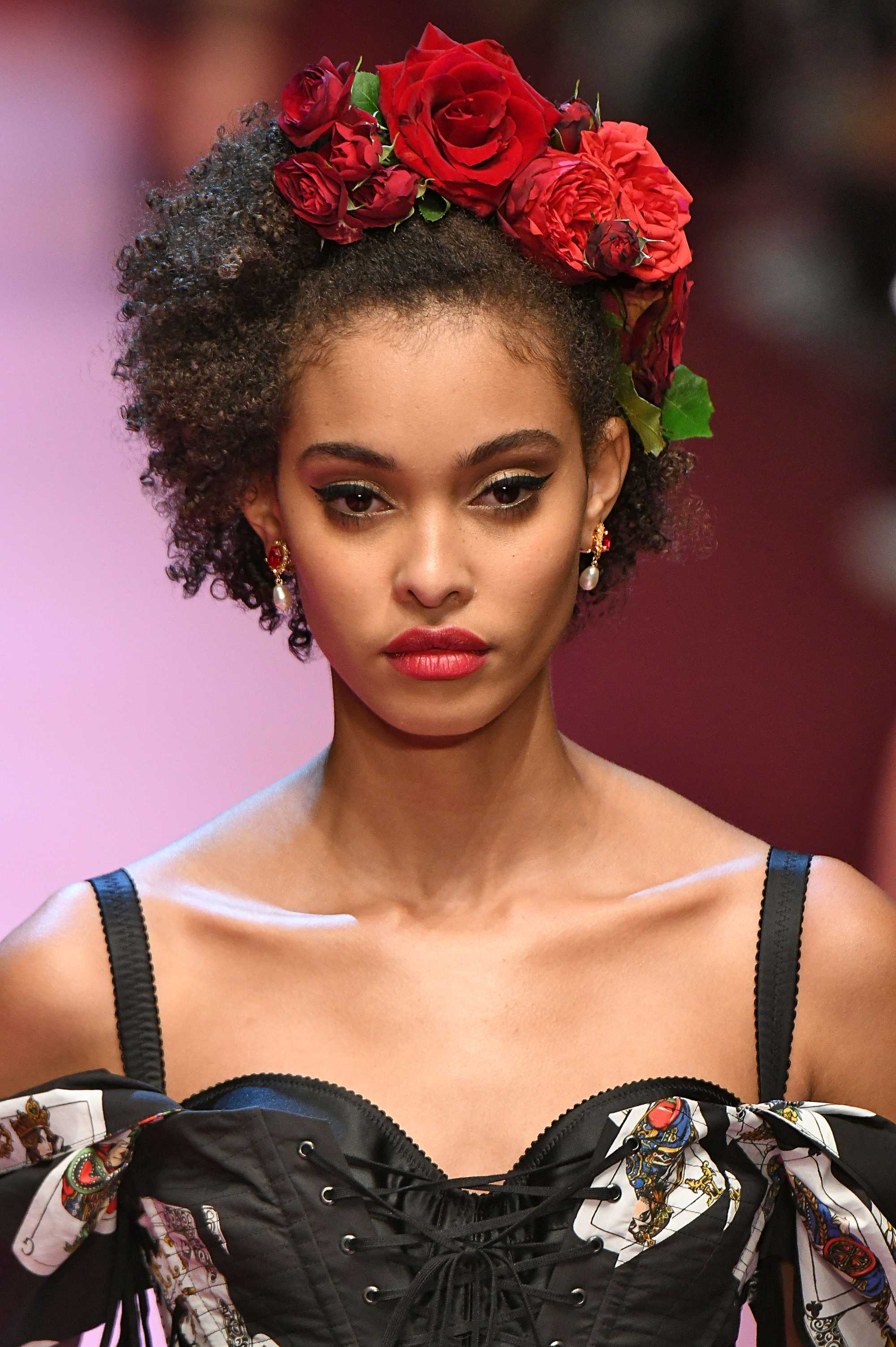 natural hair styles: close up shot of a woman with medium brown short natural hair accessorised with red roses, wearing a corset top and walking down the runway