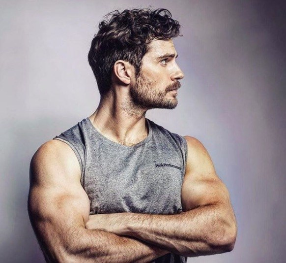side view image of Henry Cavill with a vest top on a longer textured hair