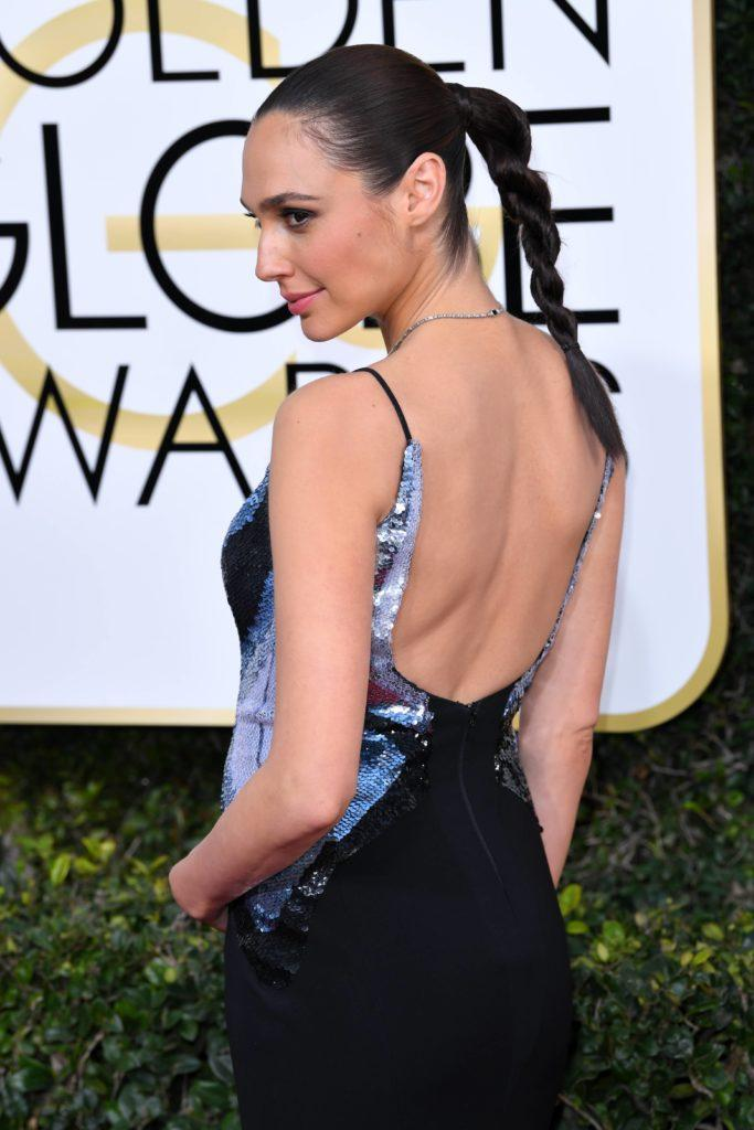 close up shot of Gal Gadot with twisted ponytail, wearing backless black dress on the golden globes awards red carpet