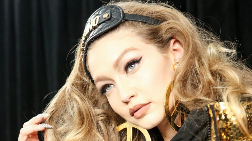 How to get thicker hair: Backstage shot of Gigi Hadid at the Moschino X H&M fashion show, with voluminous wavy blonde hair, wearing a gold puffa jacket