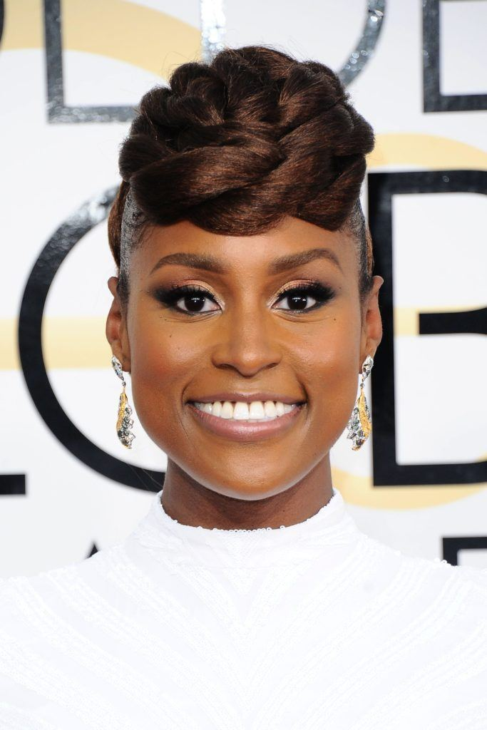 close up shot of Issa Rae with rope braid updo, wearing white dress on the golden globe awards red carpet