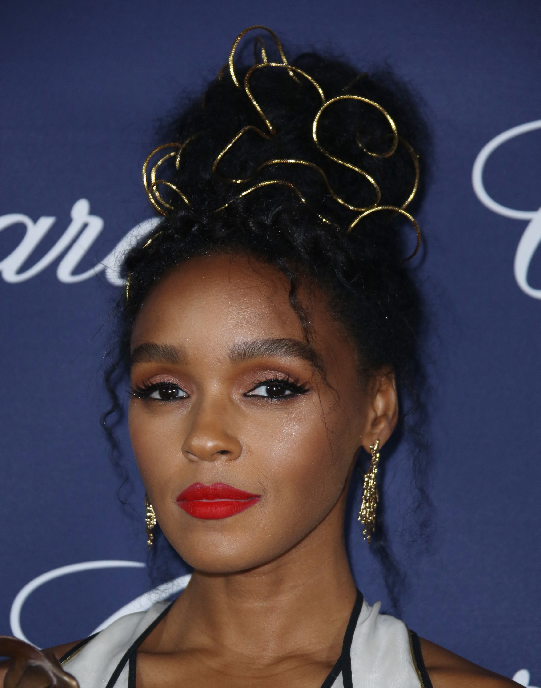 Janelle Monae wearing her hair in an updo on the red carpet with gold wires weaved in