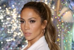 Jennifer Lopez with highlighted hair in a white suit at an event