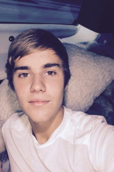 Justin Bieber talking a selfie wearing a white tshirt with a side swept man fringe in his brown hair