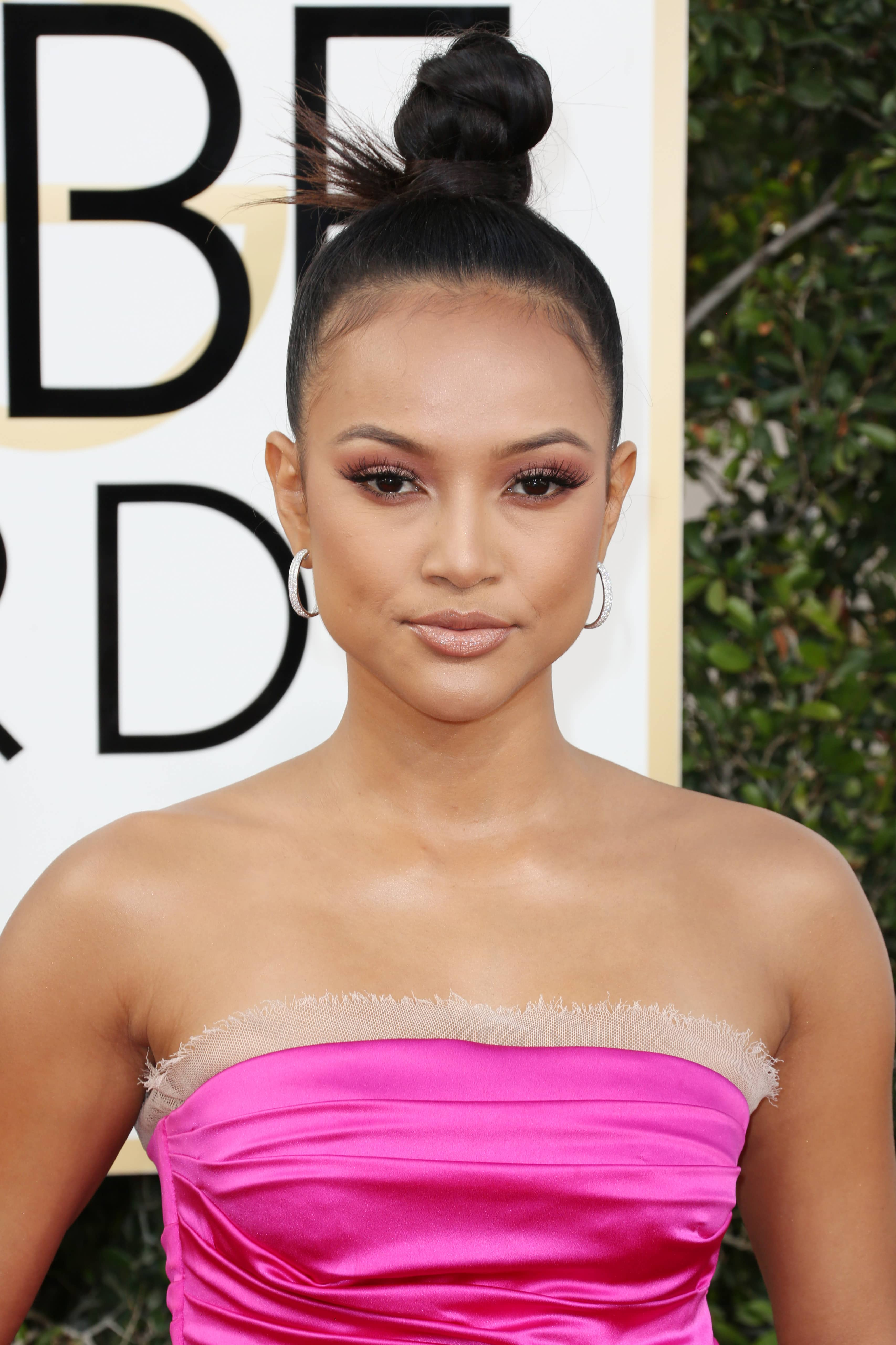 close up image of Karrueche Tran with braided top knot, wearing pink satin bandeau dress on the golden globes red carpet