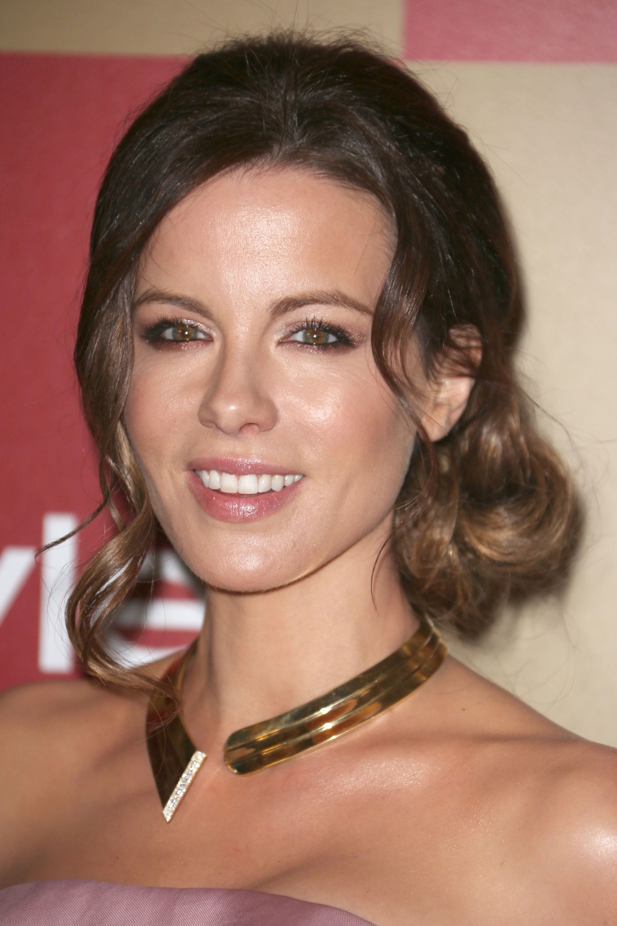 Side hairstyles: Kate Beckinsale with brunette hair in a low side bun with loose curls around her face, wearing a gold necklace