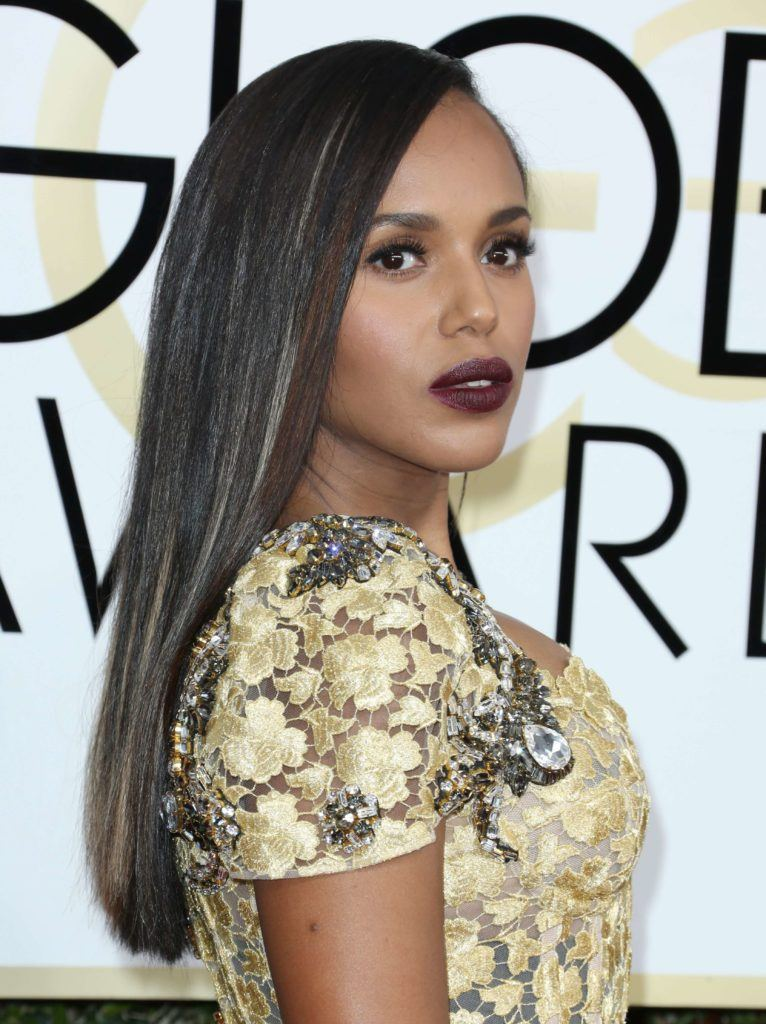 close up shot of Kerry Washington with sleek dark hair, wearing purple lipstick and yellow dress