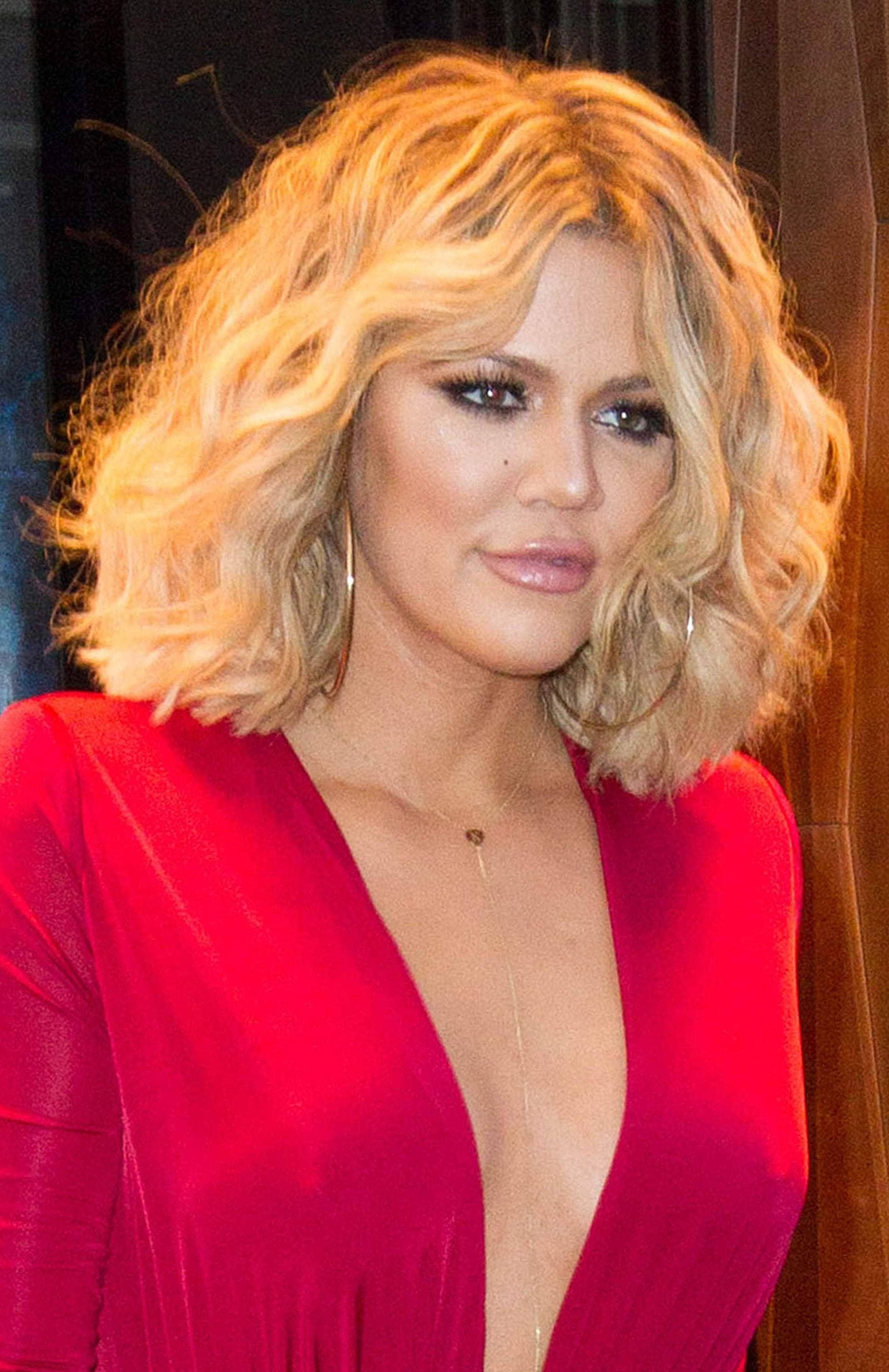 Khloe Kardashian with cury bob hair in all red