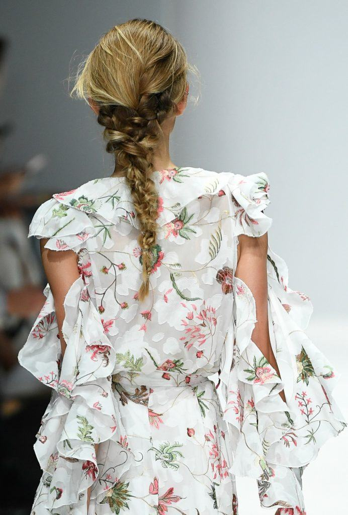 back view of a brunette model at the lana mueller berlin fashion week show with her long hair in a messy romantic braid wearing a floral cut out dress
