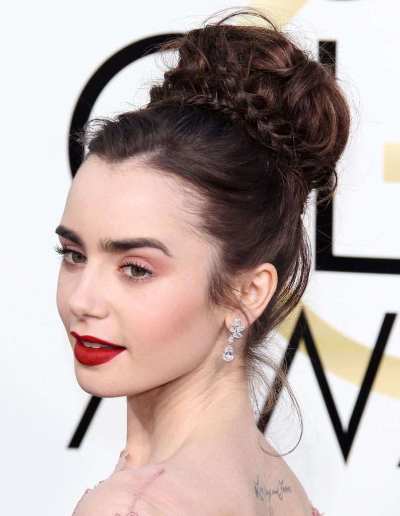 close up shot of Lily Collins with braided bun updo on the golden globes red carpet