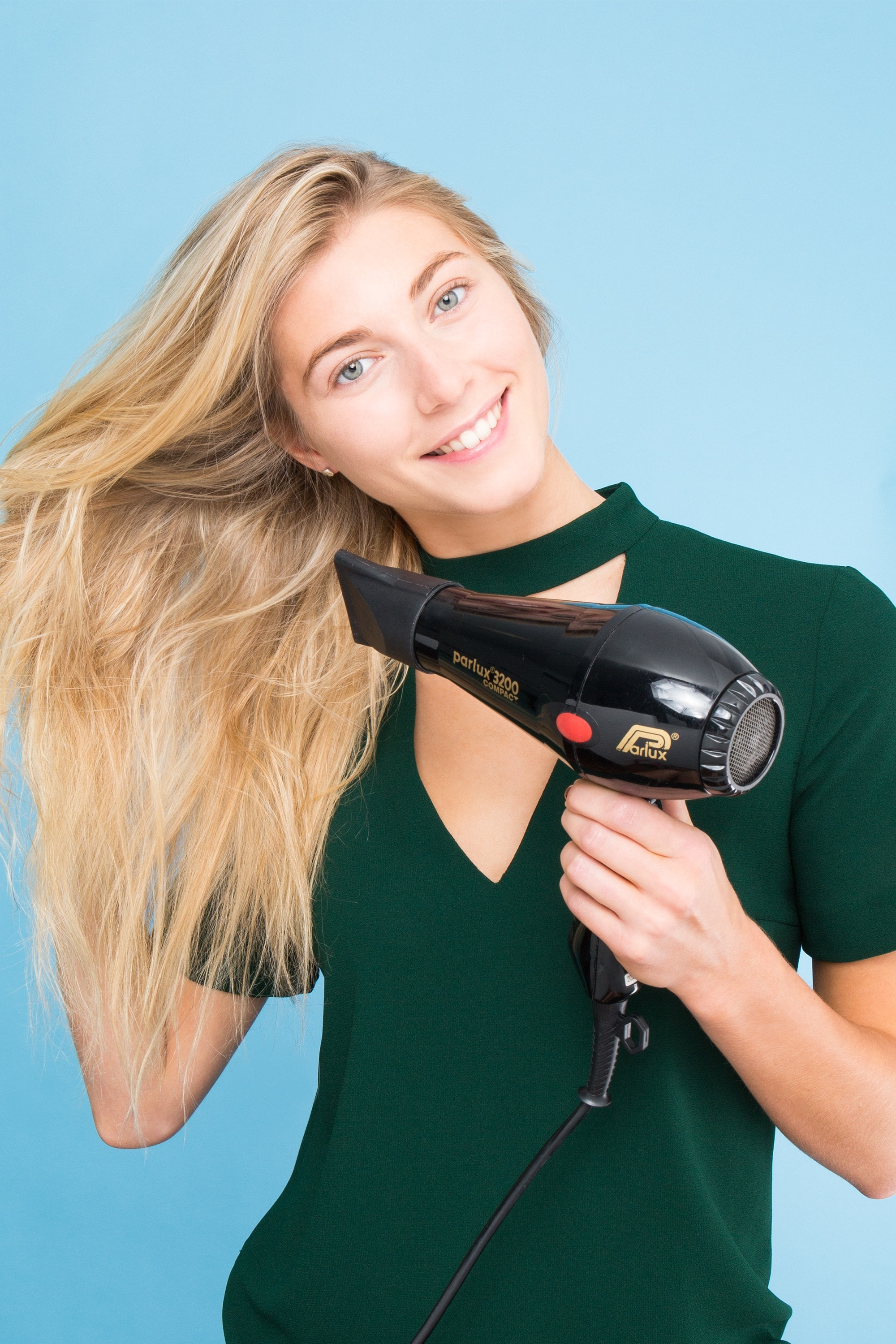 a blonde woman hairdrying her long hair in a green suit