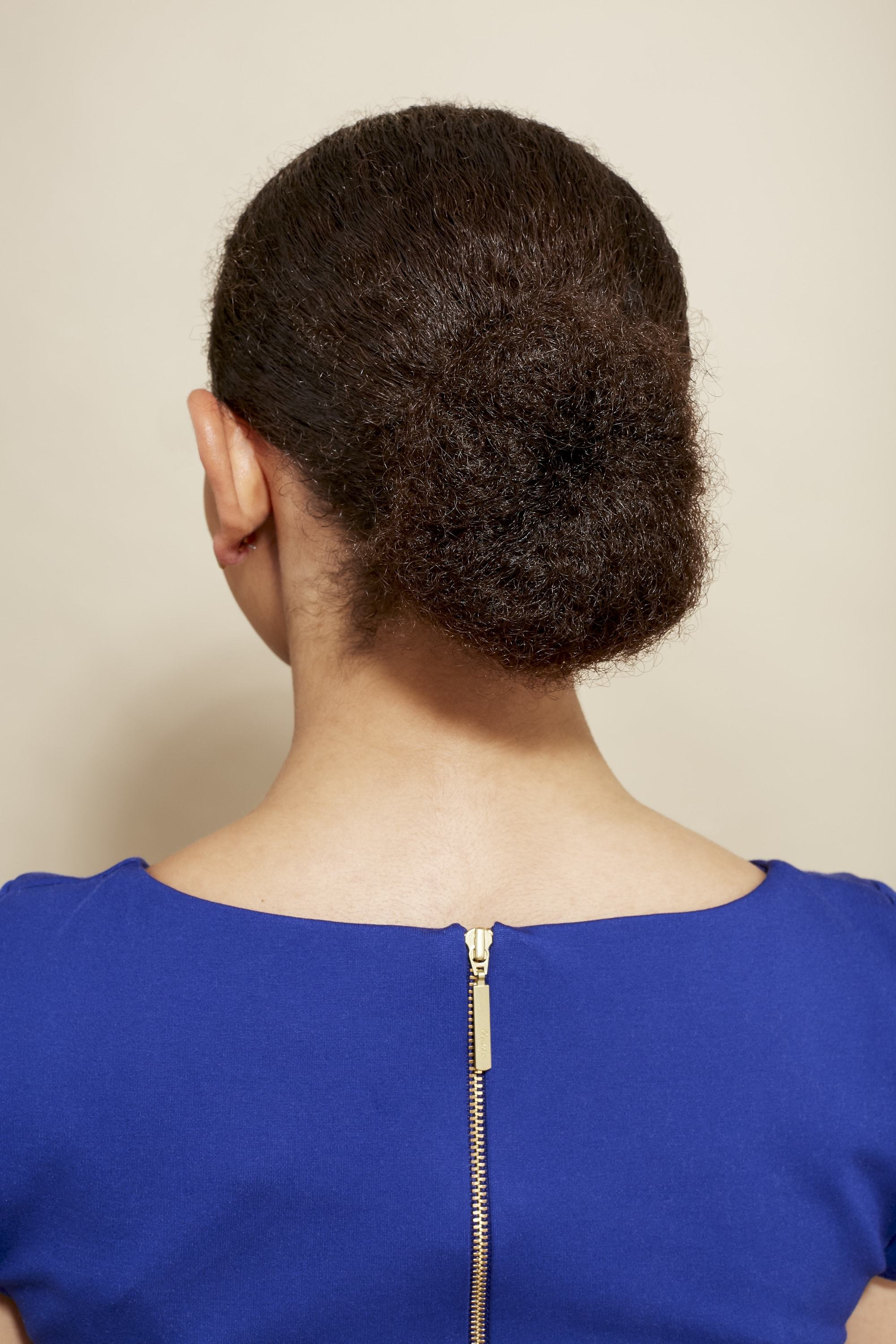 mixed race hair: close up back shot of a woman with natural medium brown hair styled into a smooth low bun, wearing a blue dress and posing in a studio setting