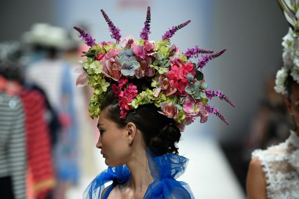 dark haired runway model at the maison common berlin fashion week show wearing a dramatic floral headpiece