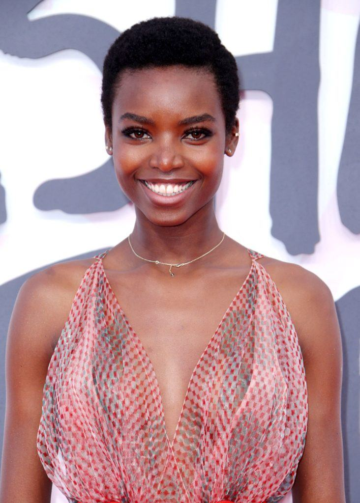 black haircuts: close up shot of maria borges with a dark brown, short side-part afro hairstyle, wearing a pink dress and posing on the red carpet