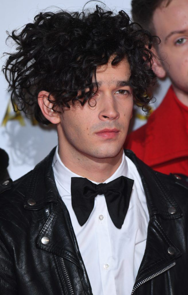 the 1975 artist Matt Healy with messy curls hairstyle in suit - cool haircuts for men
