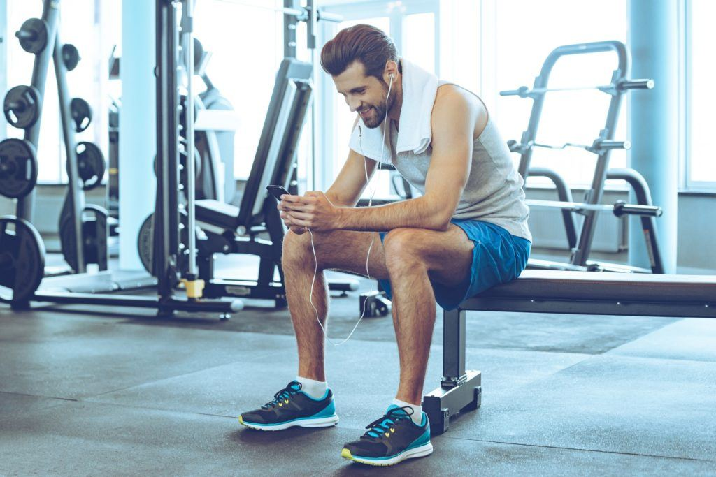 male model with slick hairstyle at gym sitting by workout equipment