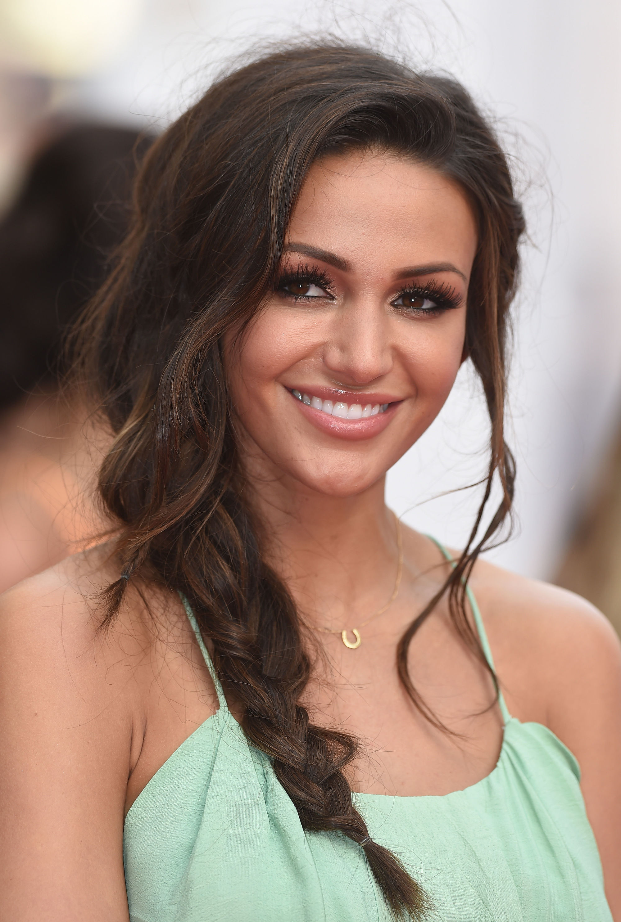 Side hairstyles: Michelle Keegan with brown hair in a Grecian inspired side braid, wearing a mint dress