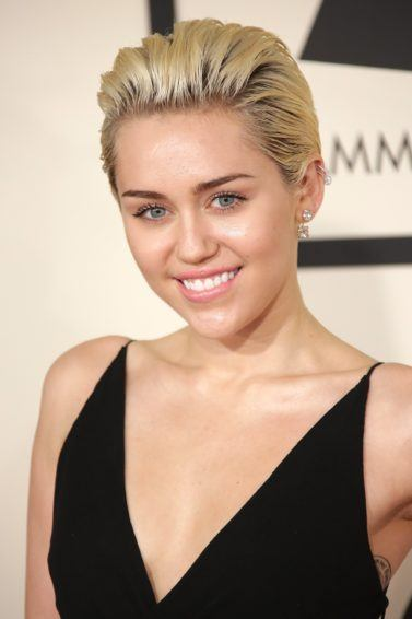 miley cyrus on the red carpet with short blonde hair swept back wearing a plunging neckline black dress