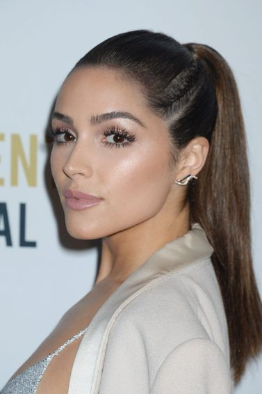 Olivia Culpo on the red carpet with her dark brown hair worn in a high ponytail with a side braid woven in