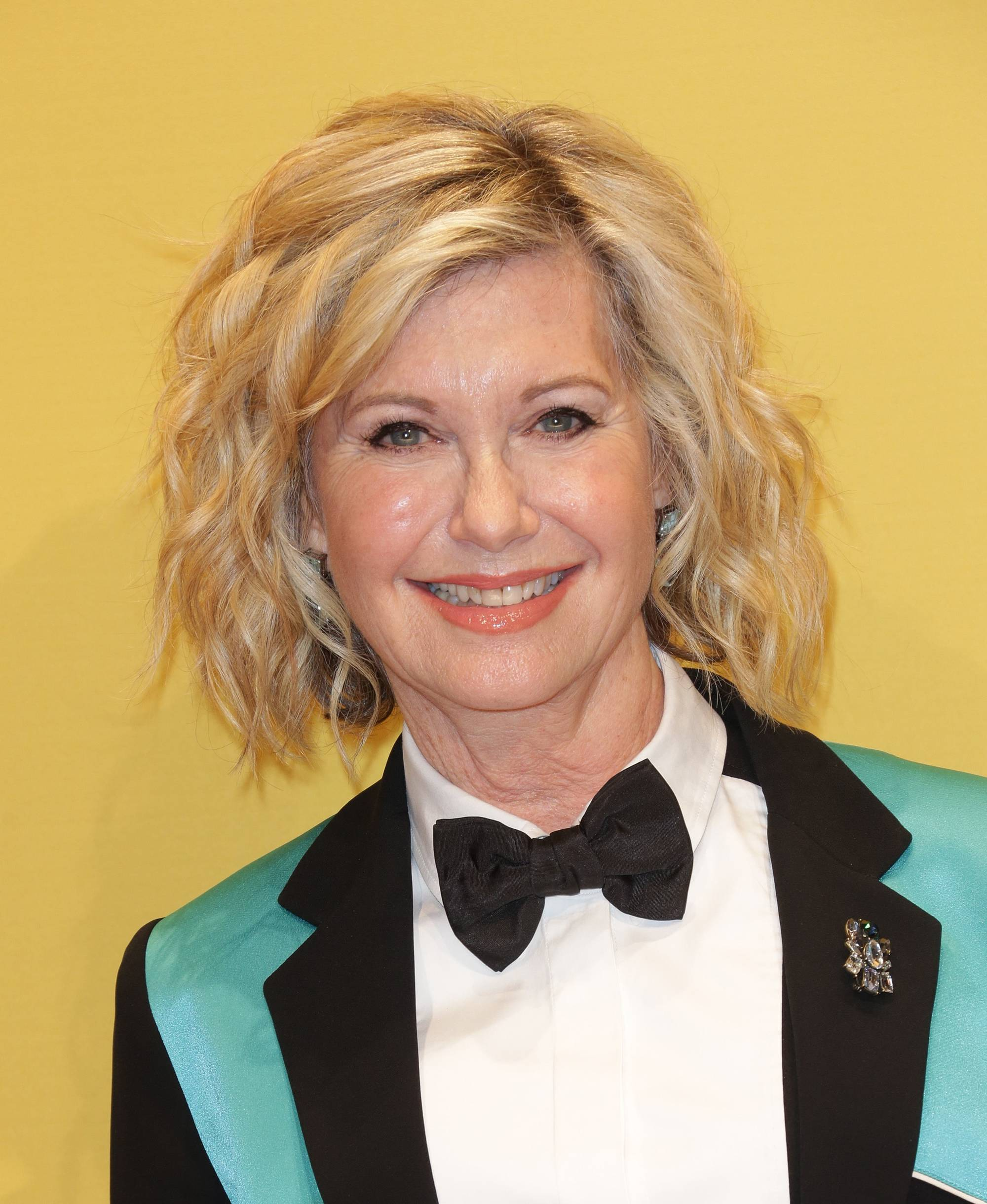 Close up of Olivia Newton John with curly bob hairstyle in teal suit