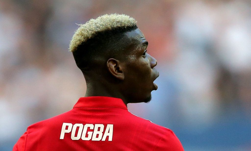 footballer hairstyles: pogba with dark brown natural hair with bleach blonde ends on football pitch