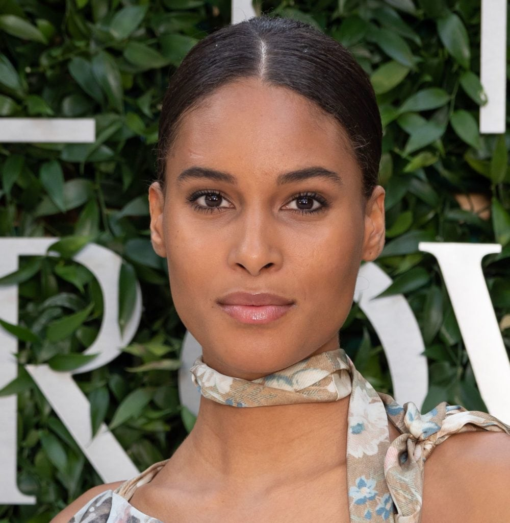 black women hairstyles: close up shot of a woman with chestnut brown sleek, relaxed hair styled into a low bun