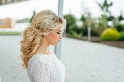 Blonde bride looking down with bouffant half-up half-down
