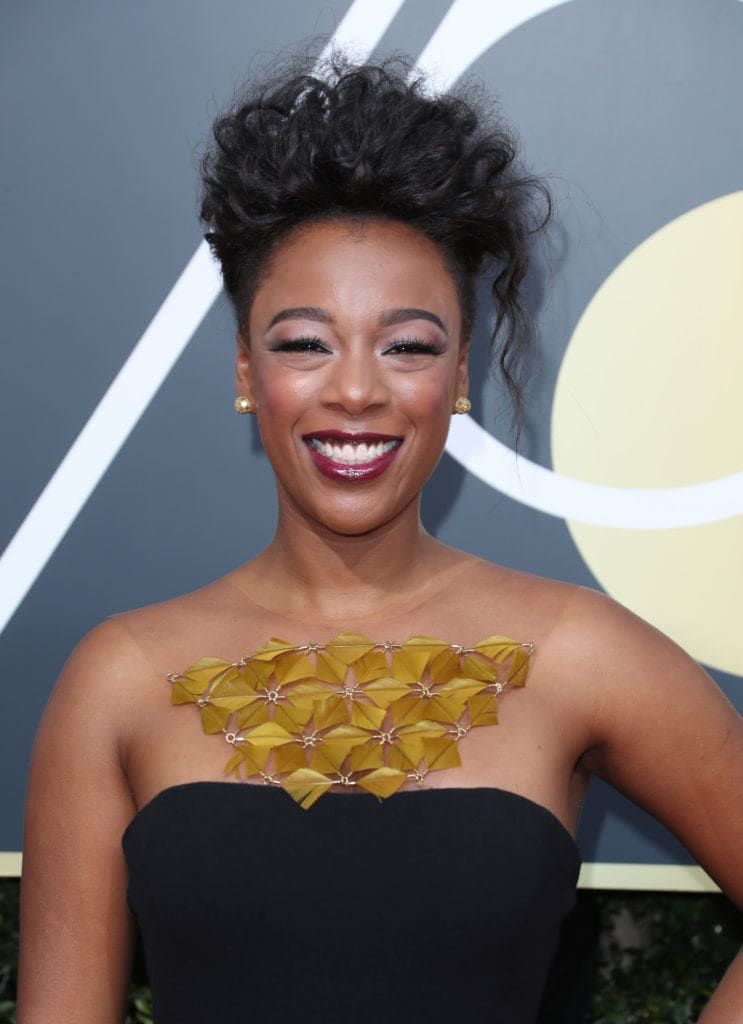 close up shot of samira wiley with curly updo, wearing black dress and golden neck accessory at the golden globe awards
