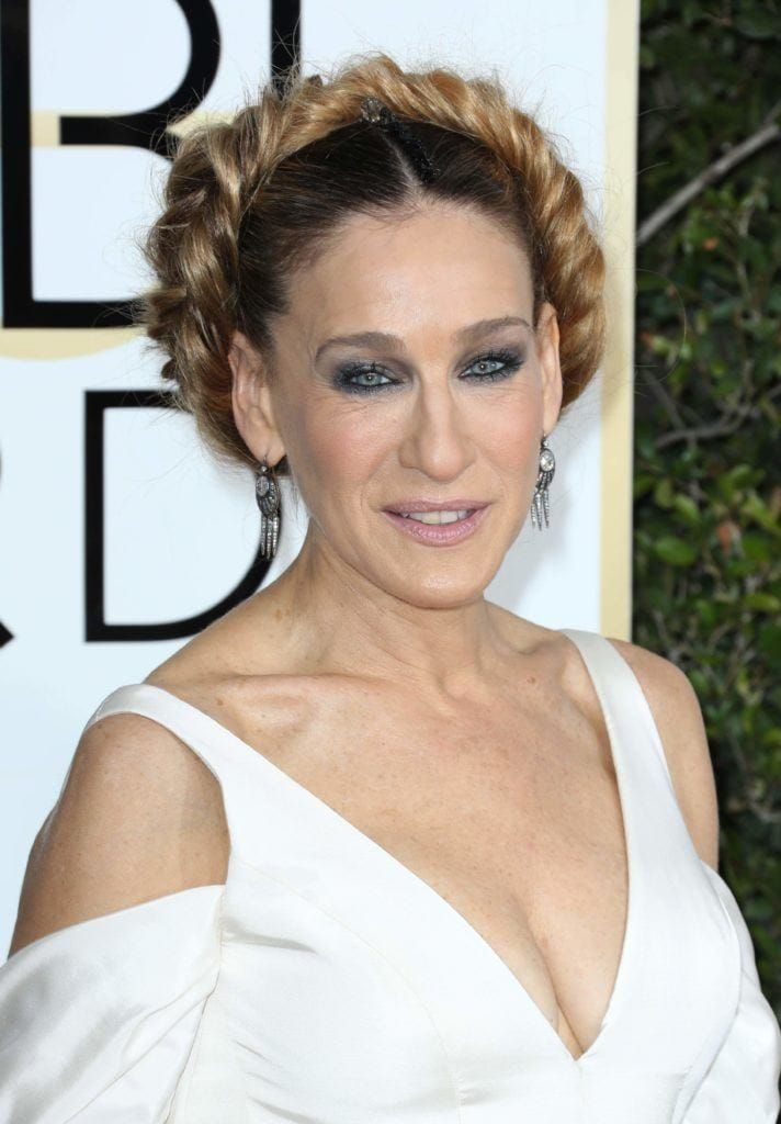 close up shot of Sarah Jessica Parker with fishtail braided crown updo, wearing white dress on the golden globes red carpet