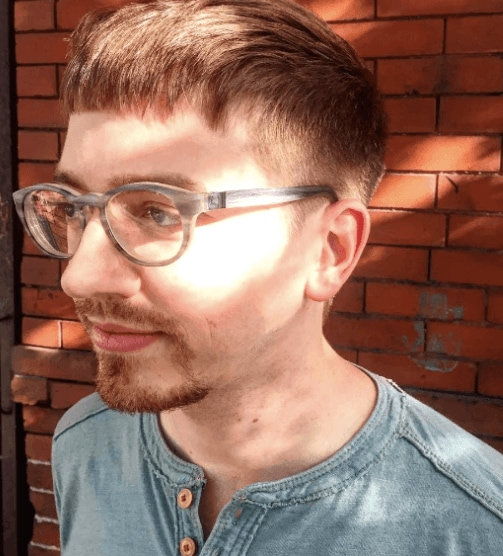 front view of a man wearing glasses with a modern ceaser haircut - cool hairstyles