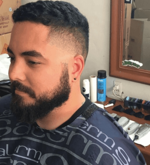 side view of a man with dark hair and a classic taper fade