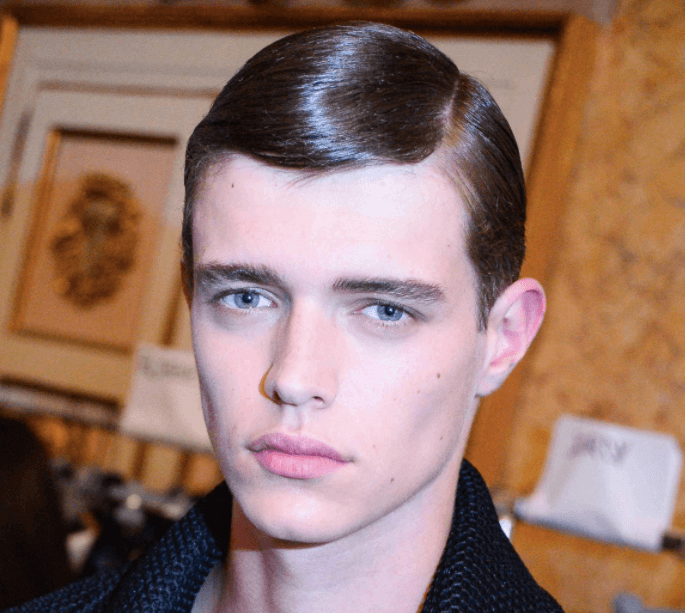 front facing image of a man with dark slick hair - parted to the side - cool haircuts
