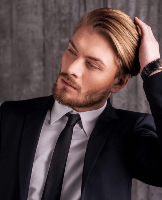 front facing image of a man with blonde hair swept back wearing a suit - cool hairstyles