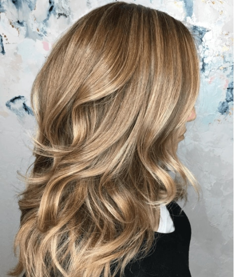 side view image of a woman with long layers and wavy hair - volume hair