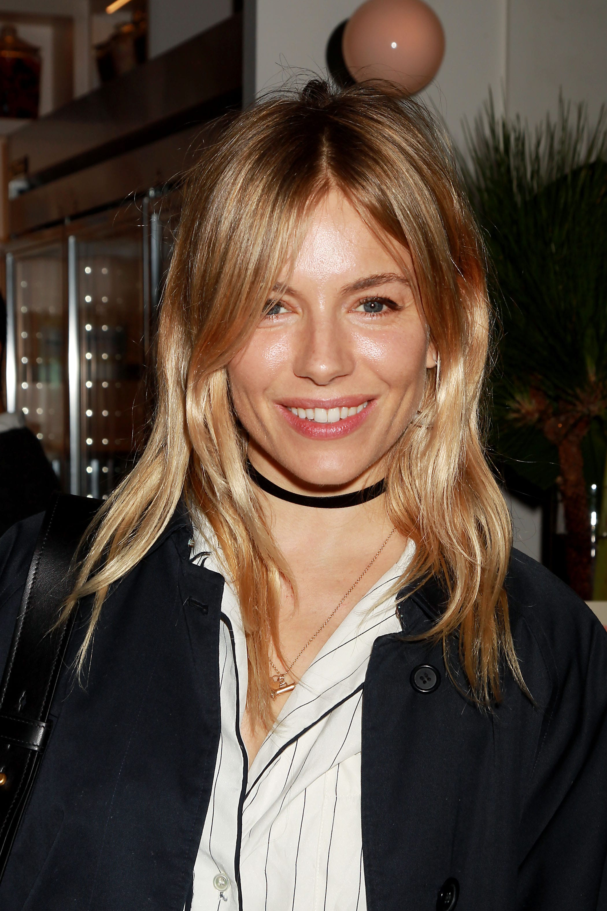 Sienna Miller at awards ceremony with iconic bangs hairstyle