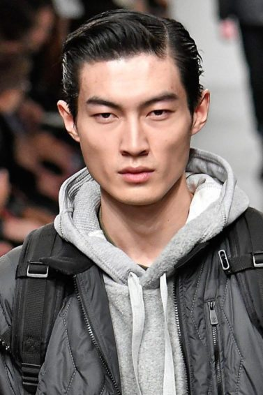 asian male model on the runway wearing a jacket and backpack with a grey hoody with his hair worn slicked back
