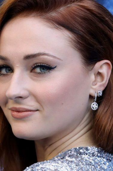 close up shot of sophie turner on the red carpet with red wavy hair
