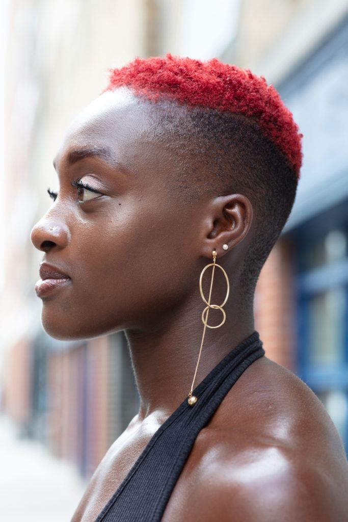 black haircuts: close up shot of woman with short, red afro hair, with a faded undercut, wearing black top with drop earrings