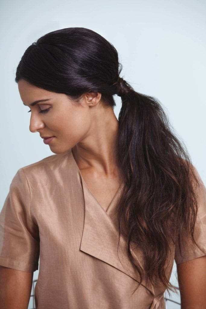 image of a woman with a low pony tail dark hair and lots of volume - volume hair
