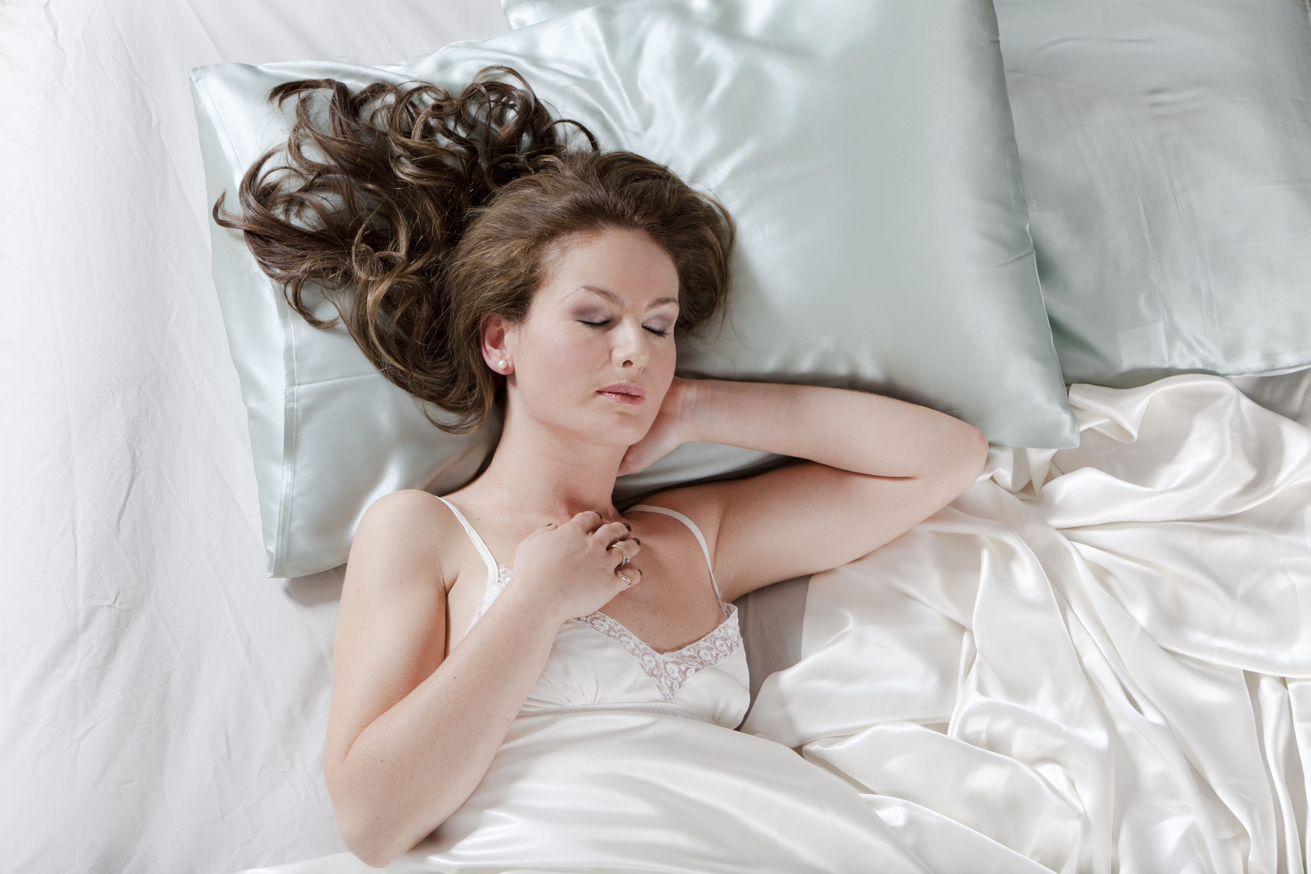 woman with long brown hair sleeping on a silk pillow