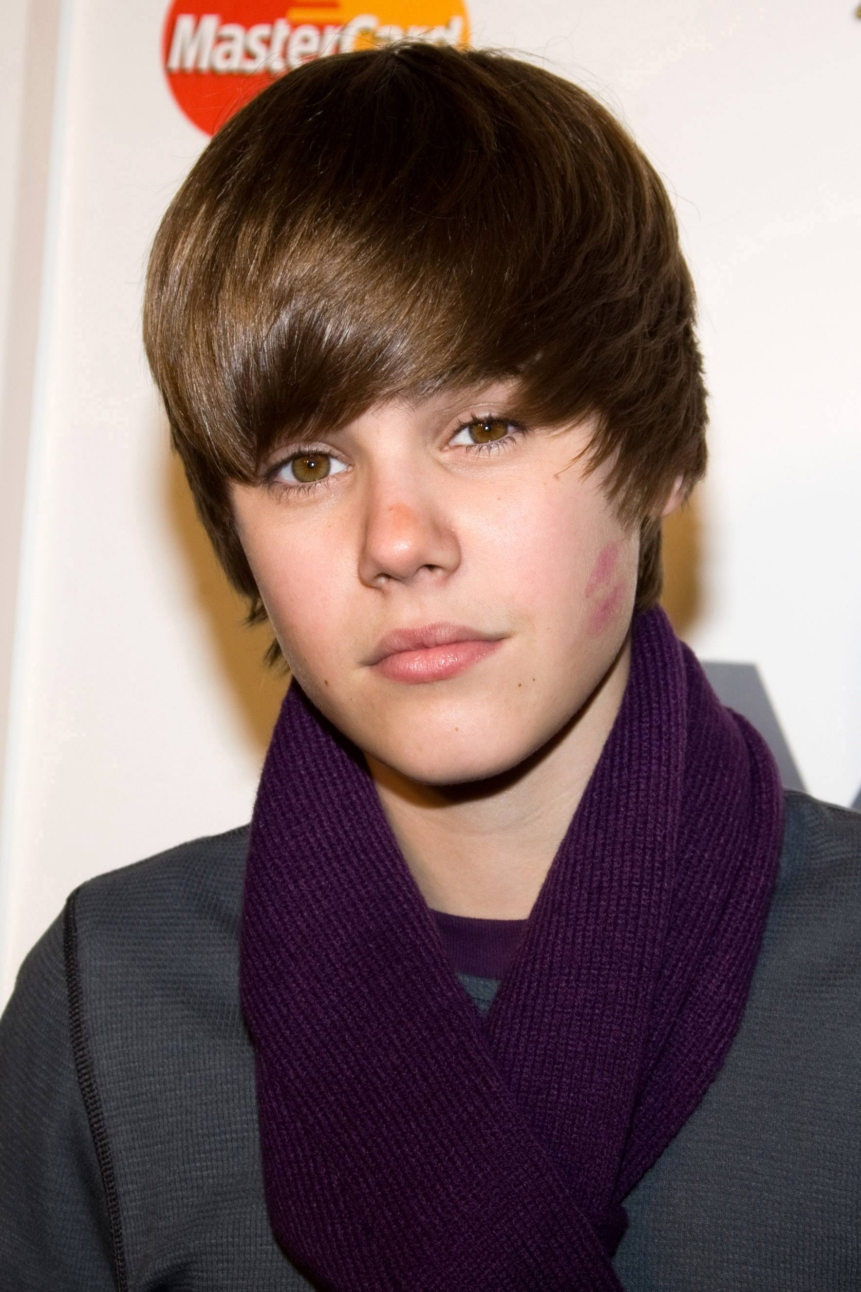 Justin Bieber with a long side swept man fringe and brown hair