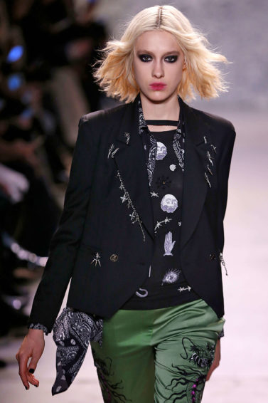 '90s grunge hairstyles on model with blonde wavy bob wearing a black top and green trousers