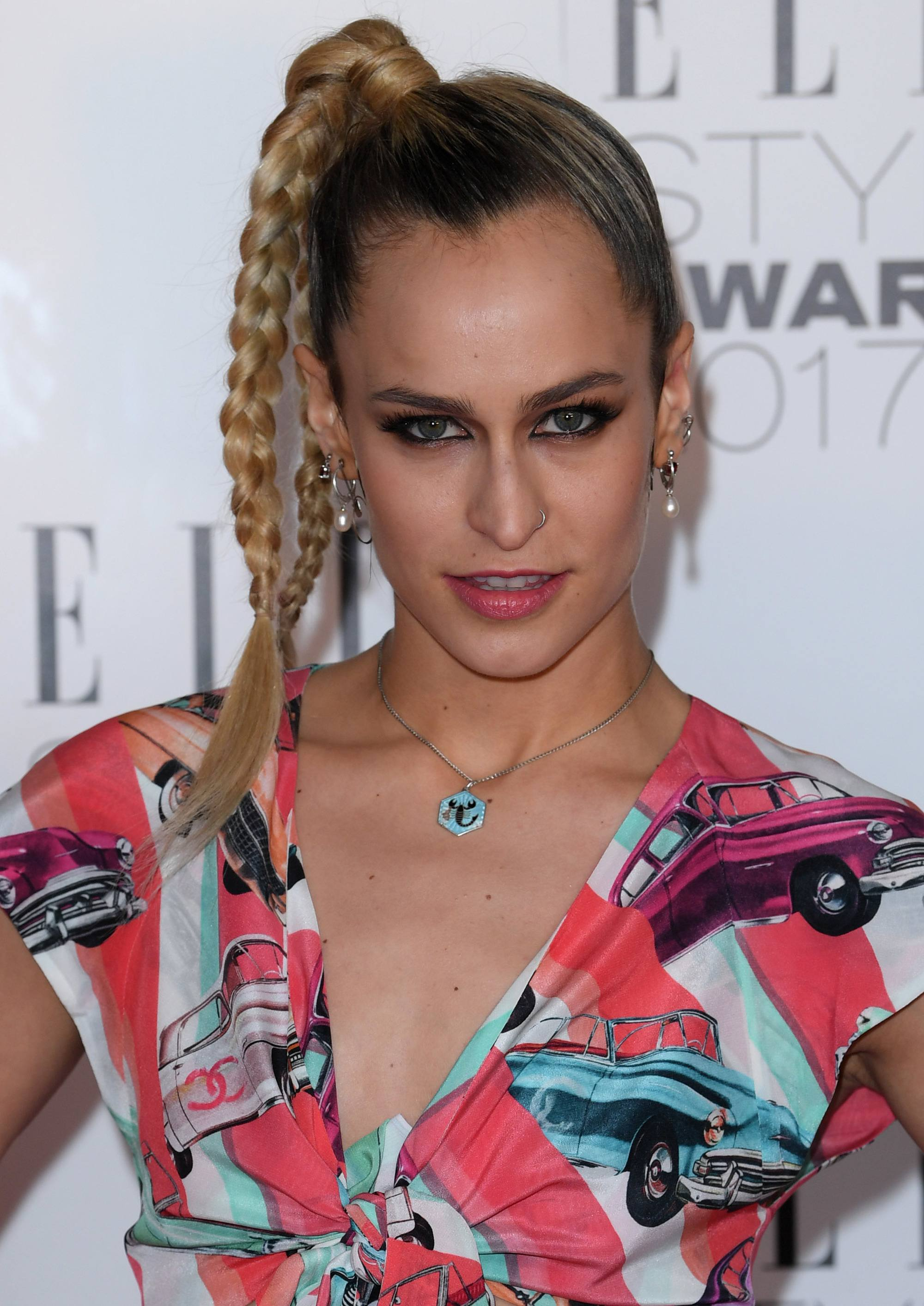 Alice Dellal at the elle style awards in a car print top with her blonde hair styled in a braided ponytail